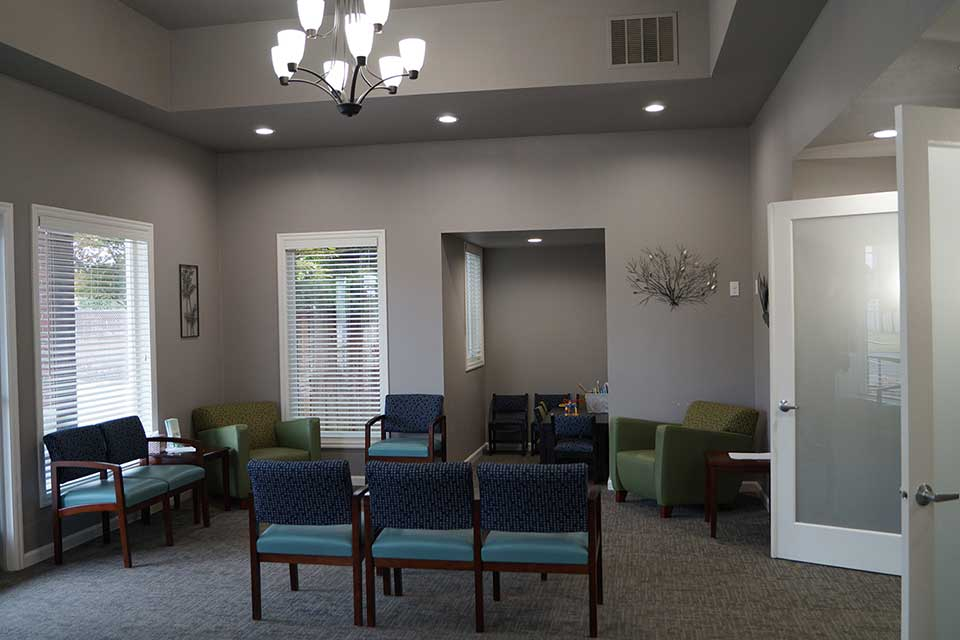 Waiting area with chairs and reception desk at Calapooia Family Dental