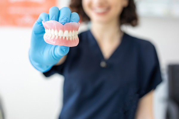 Woman holding a set of dentures