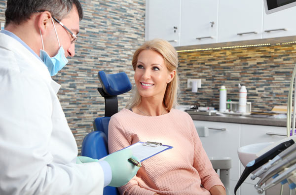 Woman talking to dentist during dental exam at Calapooia Family Dental in Albany, OR